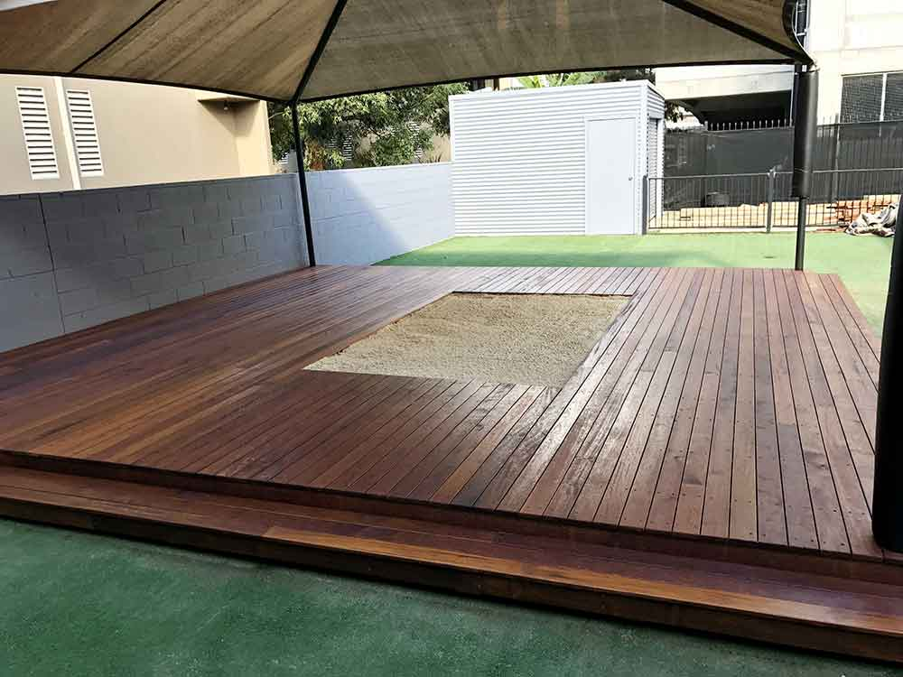 Timber decking around sandpit