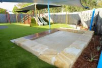 bark pit and custom seat with timber and sandstone natural elements