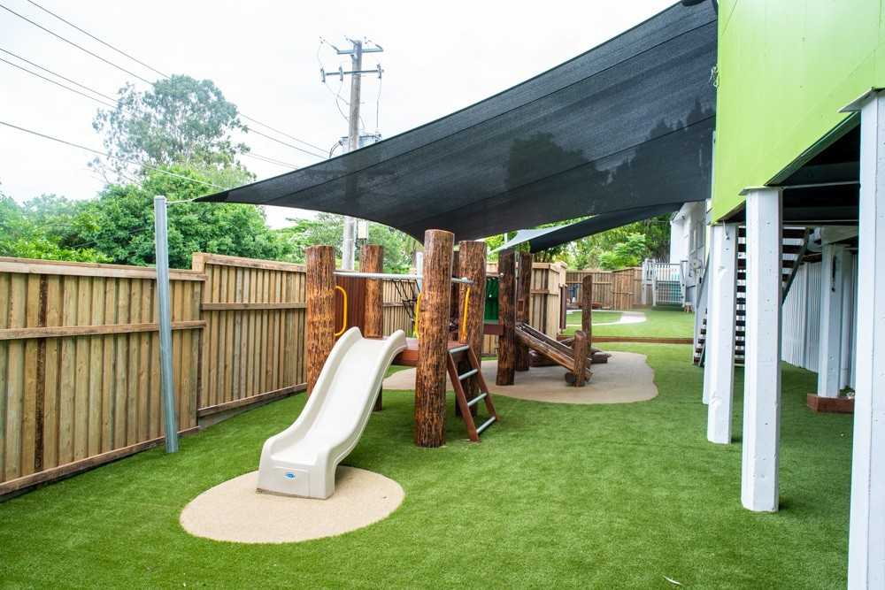Log fort with slide and climbing wall on wet pour & astroturf