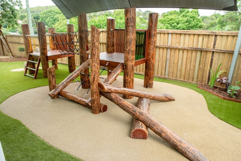 Log fort with slide and climbing wall on rubber mat & astro